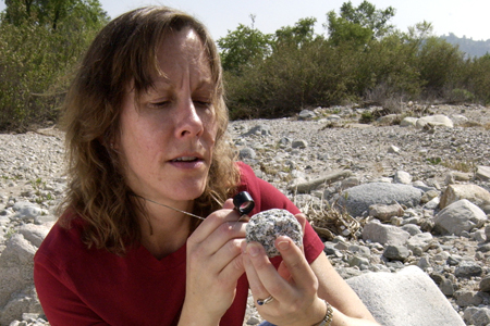 Joy Crisp, working on the next generation Mars Rover, takes a closeup look at a rock with a geology hand lens. [Photo courtesy of NASA/JPL-Caltech]