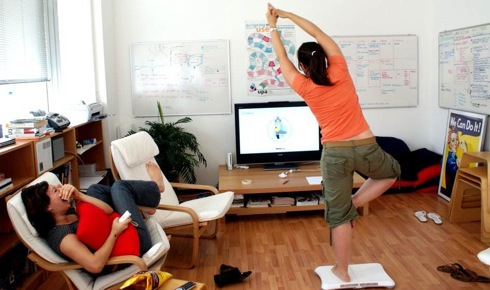 This customer practices a yoga pose using Wii Fit.  Researchers say the gaming system could provide a new <br> kind of physical therapy for patients suffering from neurodegenerative diseases. [Credit: enfad, flickr.com].