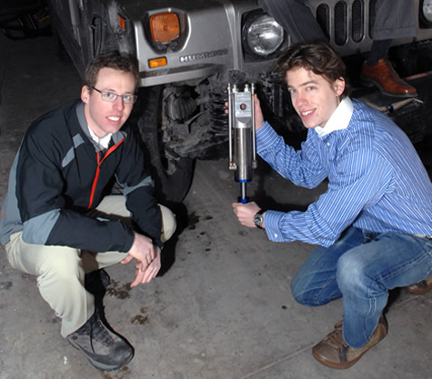 GenShock, a power-producing shock absorber, was designed by a team of MIT students including Ryan Bavetta (left) and Zack Anderson (right). [Credit: Donna Coveney, MIT]