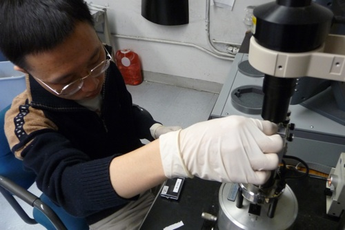 Researcher Hongzhou Gu places a DNA sample in the atomic force microscope for inspection. [Credit: Robert Goodier] Below left, An image captured by the atomic force microscope of the DNA origami to hold a robotic arm. [Credit: Hongzhou Gu]