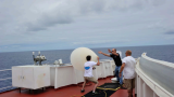 Struggling with a weather balloon on the prow of a ship