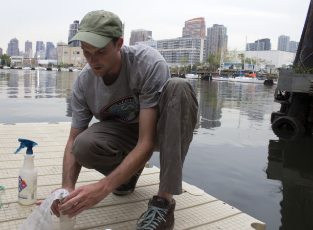 Willis Elkins sets up to collect plankton from a dock on Newtown Creek  in Brooklyn, New York. Image credit: JoAnna Klein.