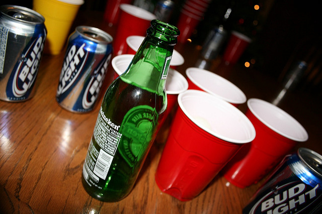 Beer cans and red solo cups on a wooden table