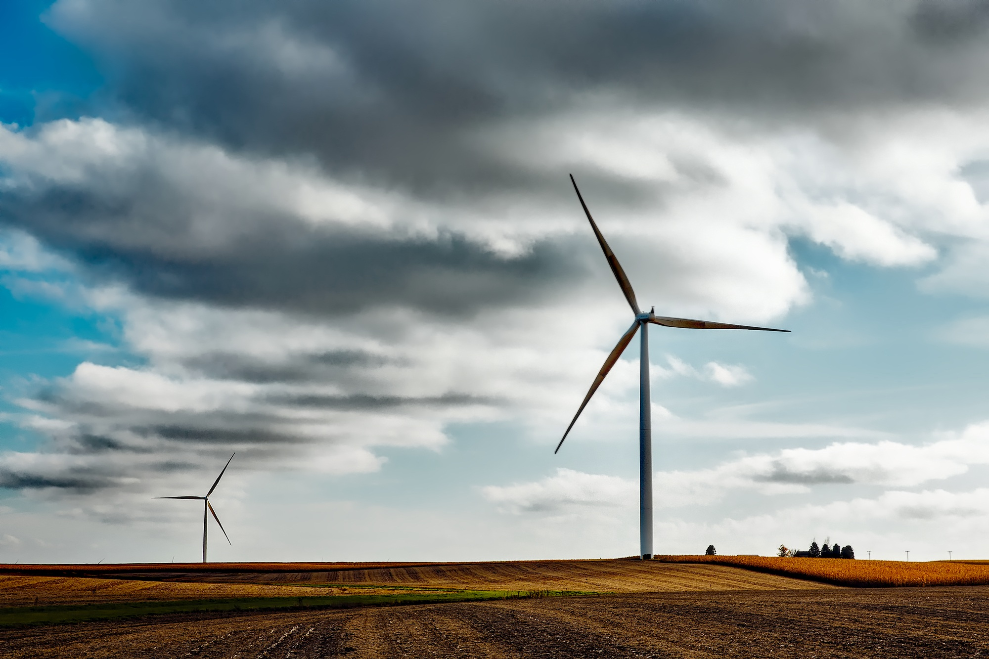 Two windmills stand in a field