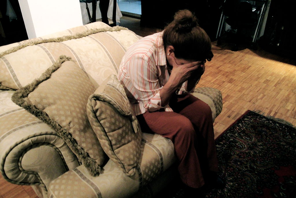 A depressed woman holds her face in her hands