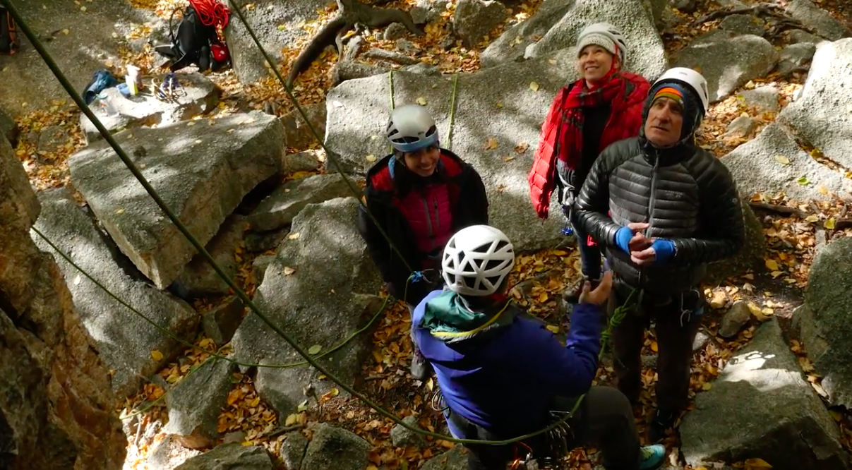 Three climbers look up at an outdoor rockbclimbing route while their instructor explains.
