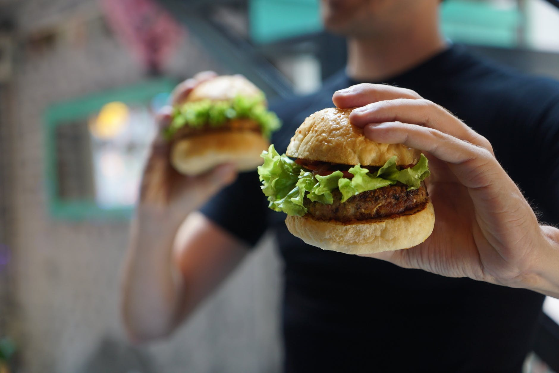 A person holding two burgers