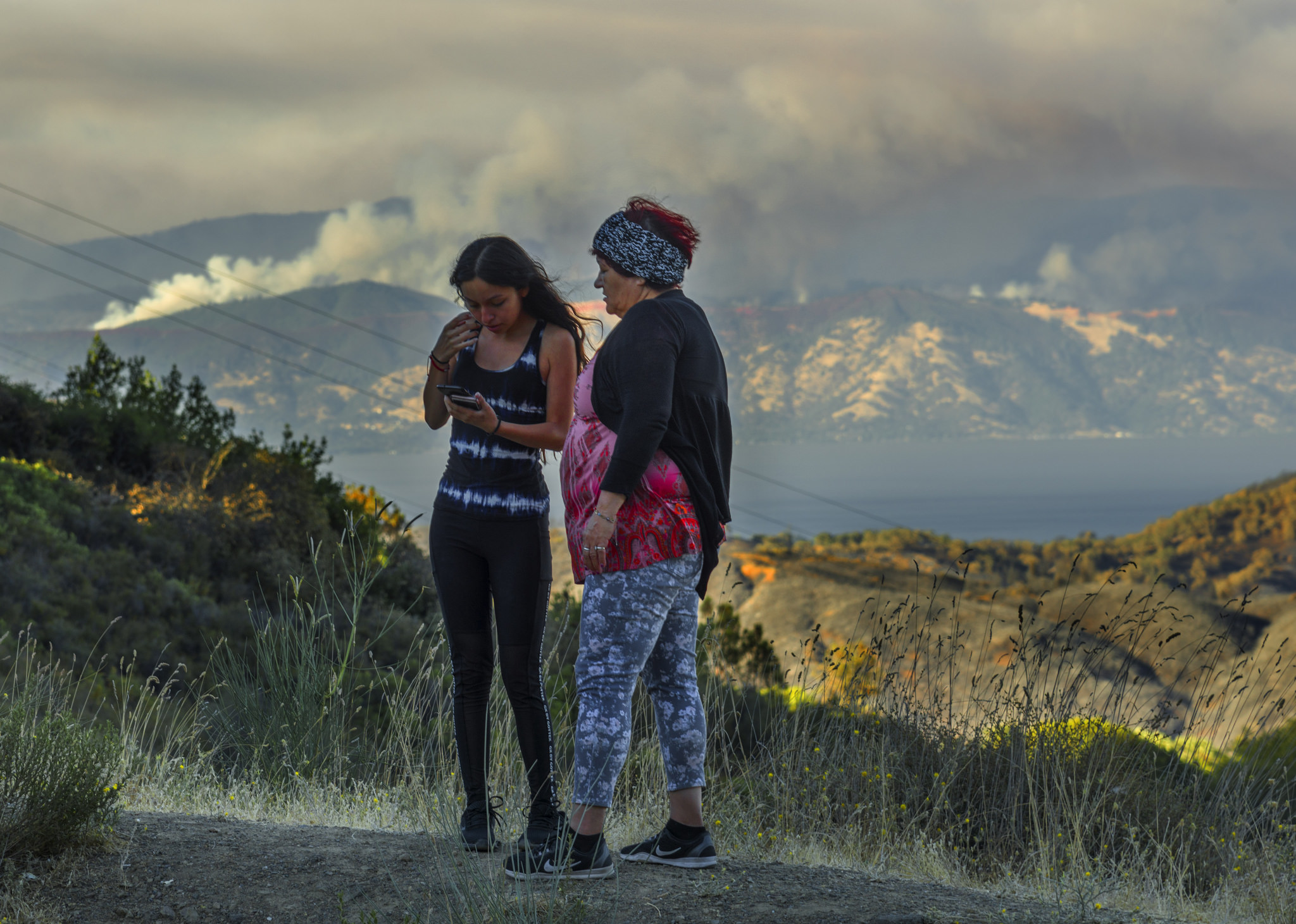 Two people look at a cellphone on the side of a road as a large wildfire burns in the background.