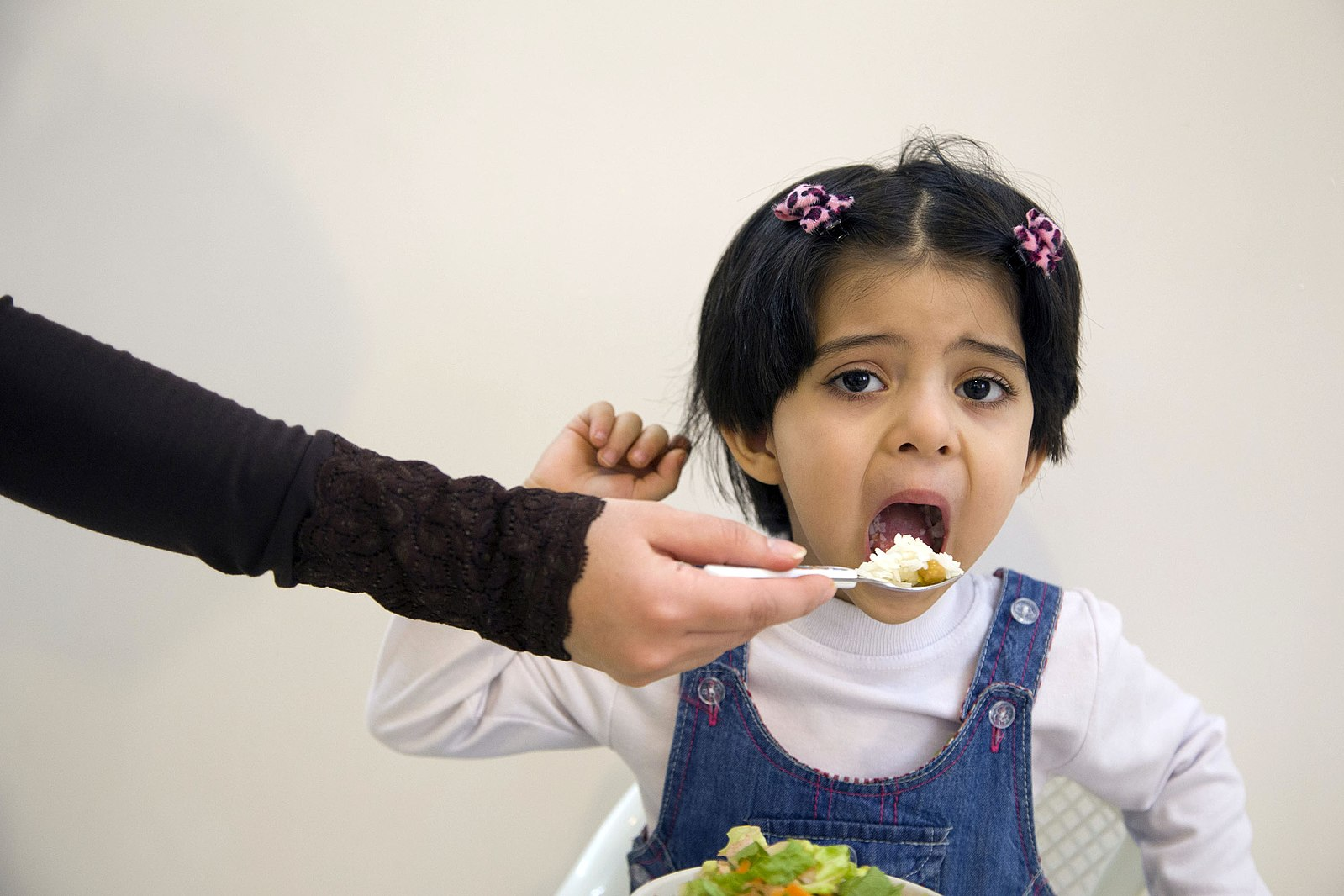 unhappy child takes a bite of food