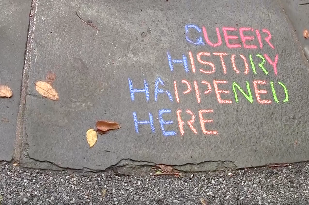 """Queer history happened here,"" written in chalk on ground."