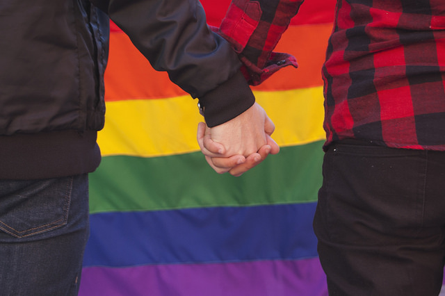 Two men hold hands in front of rainbow flag.
