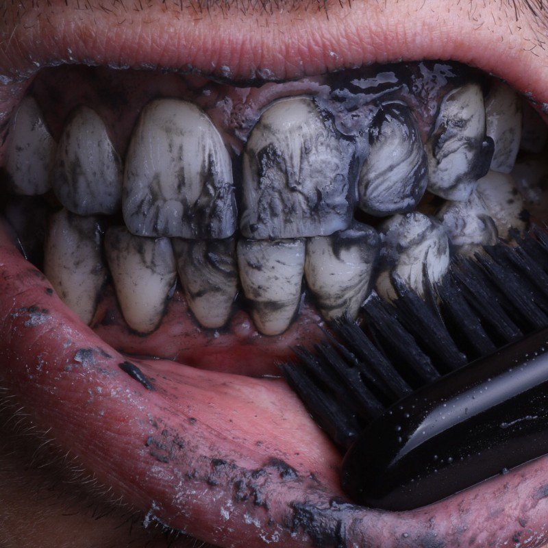 a black toothbrush scrubs black paste over teeth