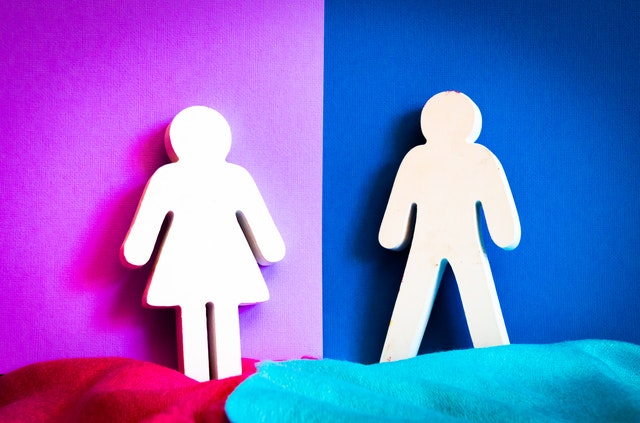 "A ""woman"" symbol is on a pink background, next to a ""man"" symbol on a blue background."