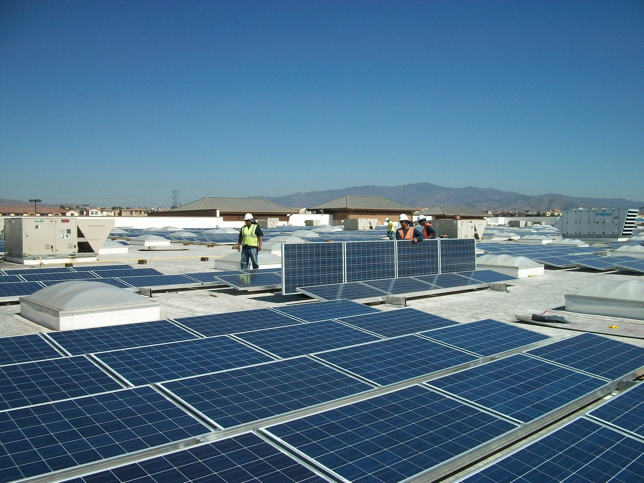 Workers installing solar panels on the roof of Walmart in Chula Vista, Calif.