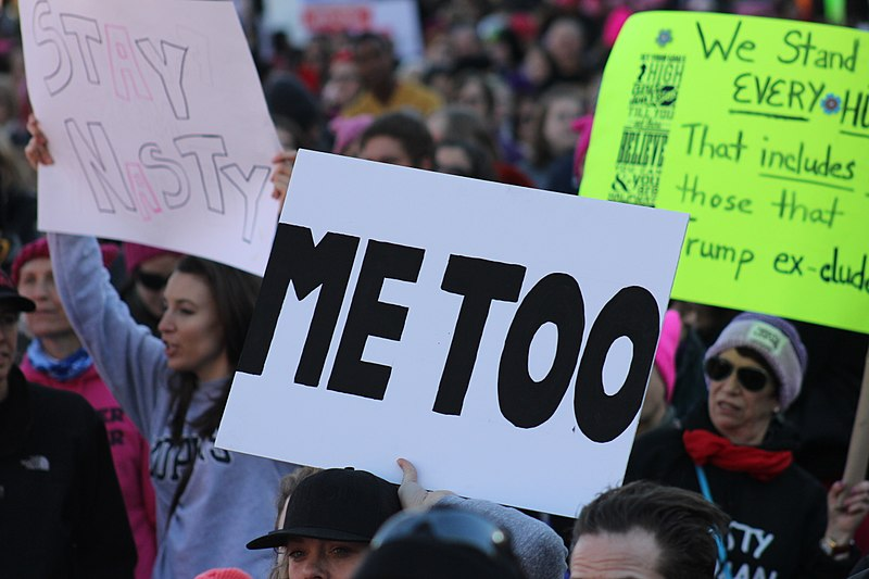 Protestors march with #MeToo poster board at Women's March in Baltimore, 2018
