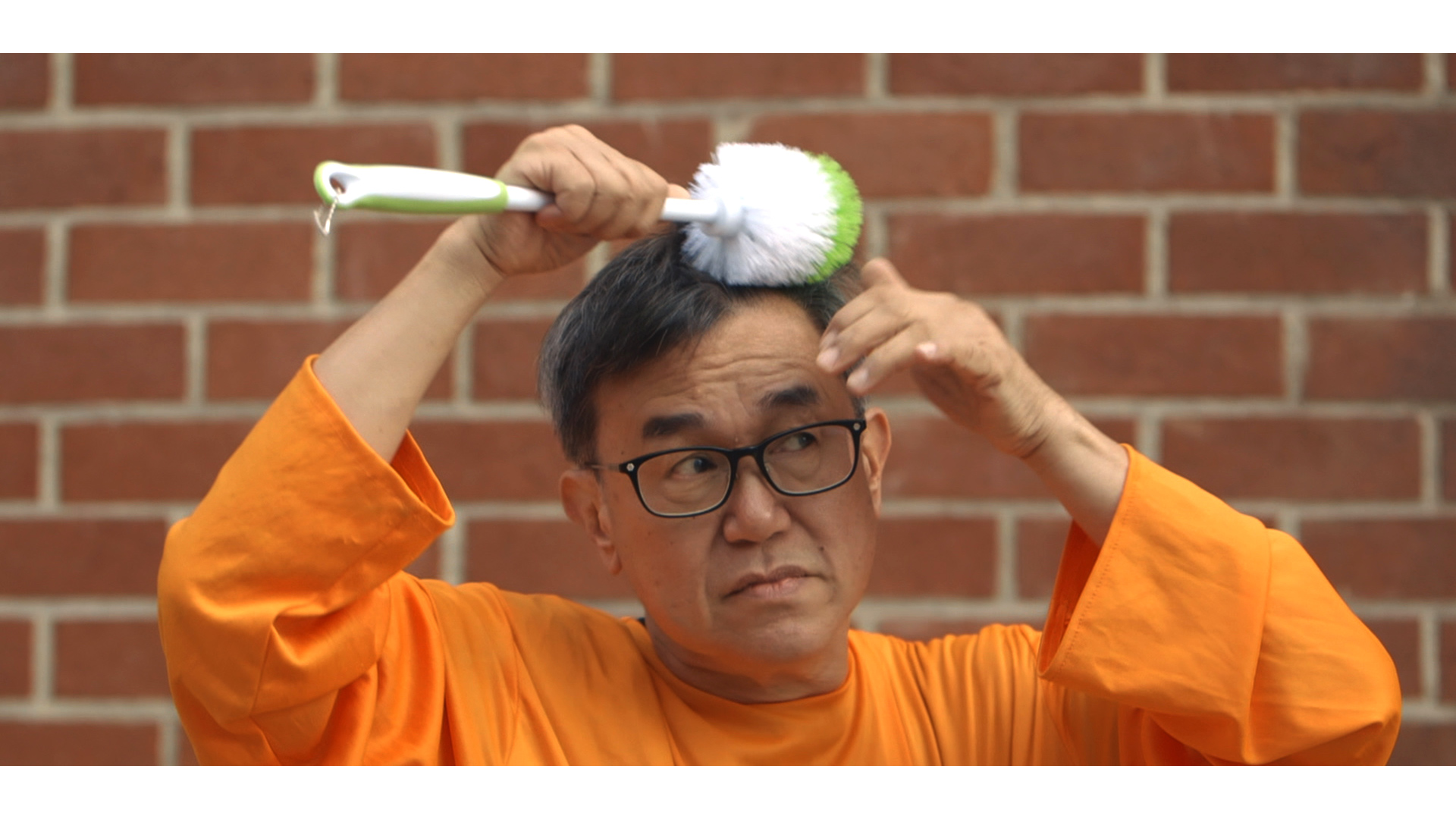 Jack Sim [Mr. Toilet] brushes his hair with a toilet wand.