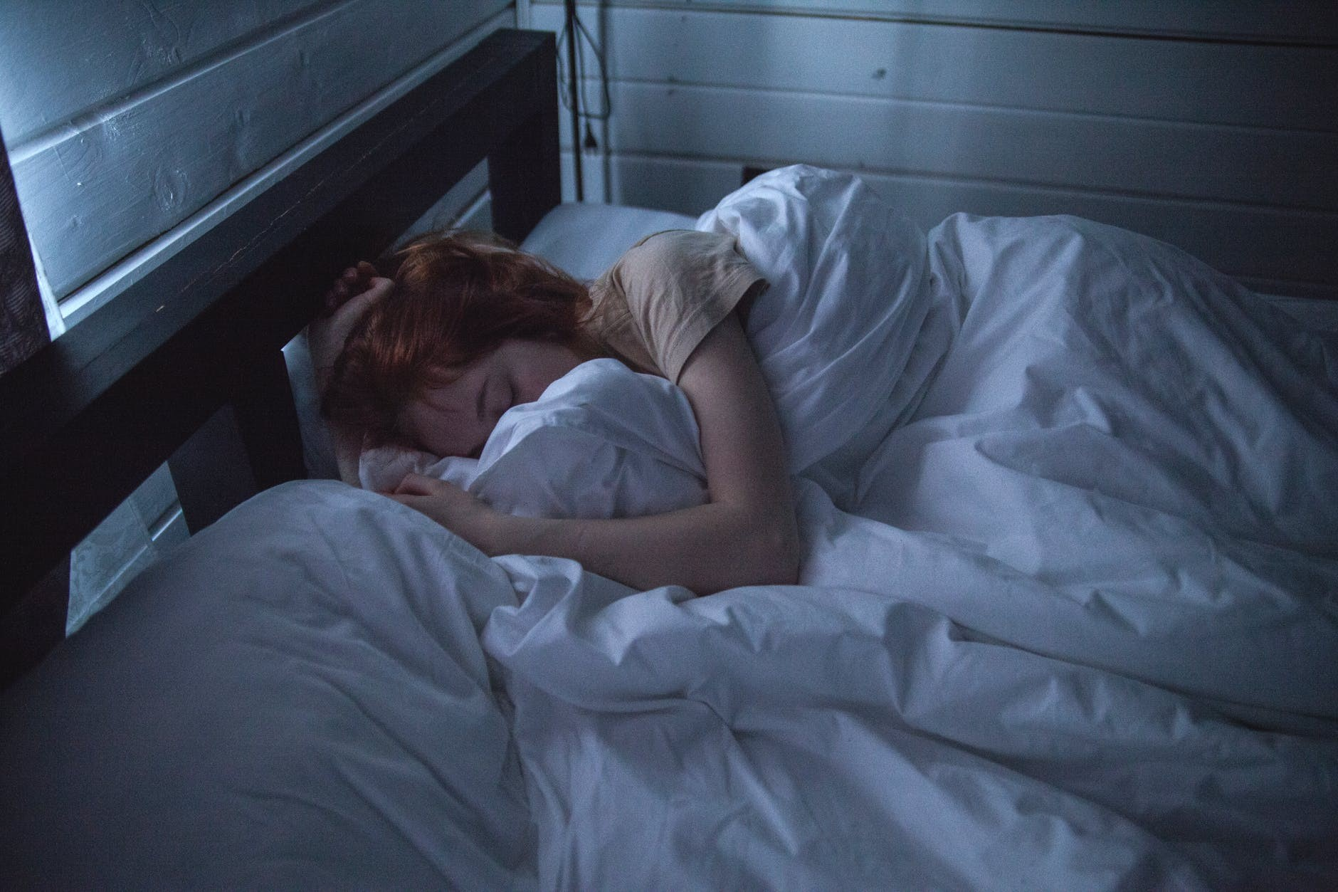 A young woman sleeps on a double bed in a dark room, her face buried in the covers.