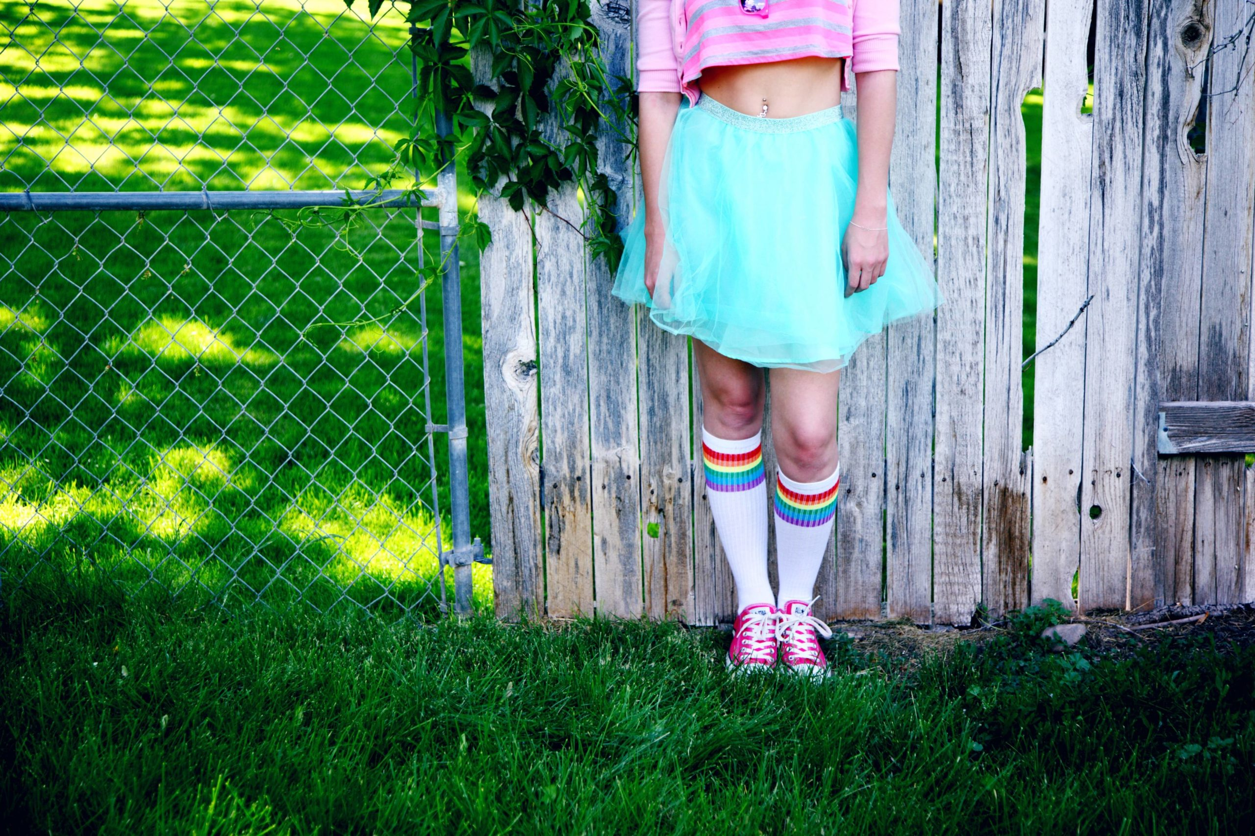 A feminine person stands in front of a wooden fence with a blue skirt, pink crop top and rainbow tube socks