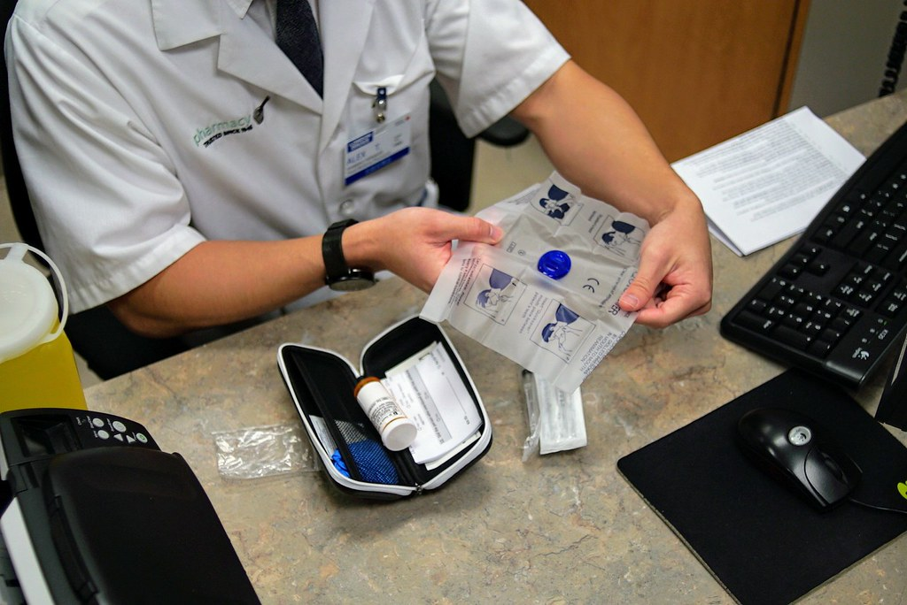 A medical worker packaging a naloxone kit