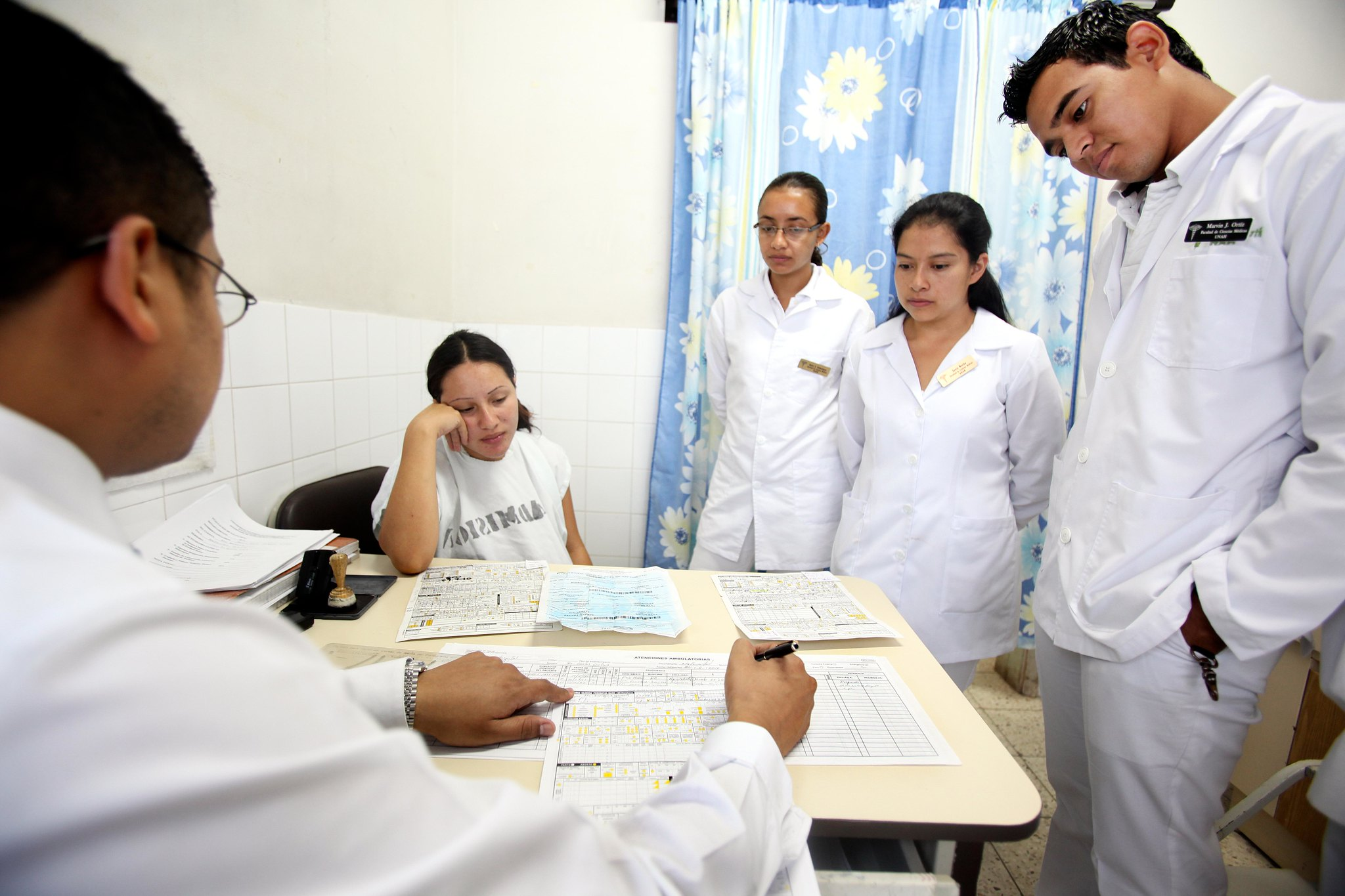 Medical professionals gather around a set of documents
