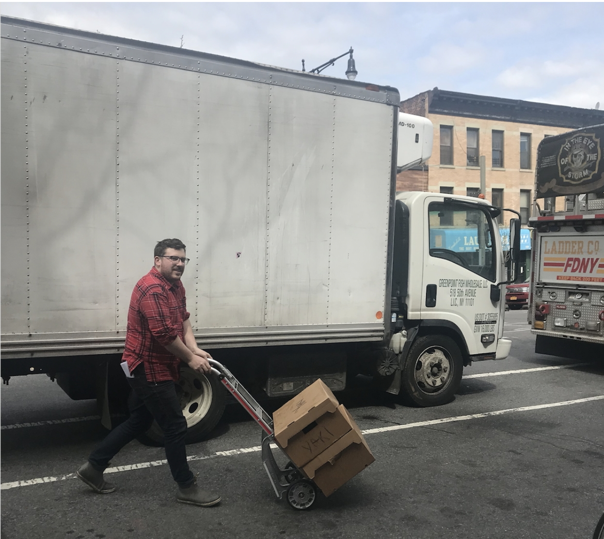 man pushing dolly in front of delivery truck