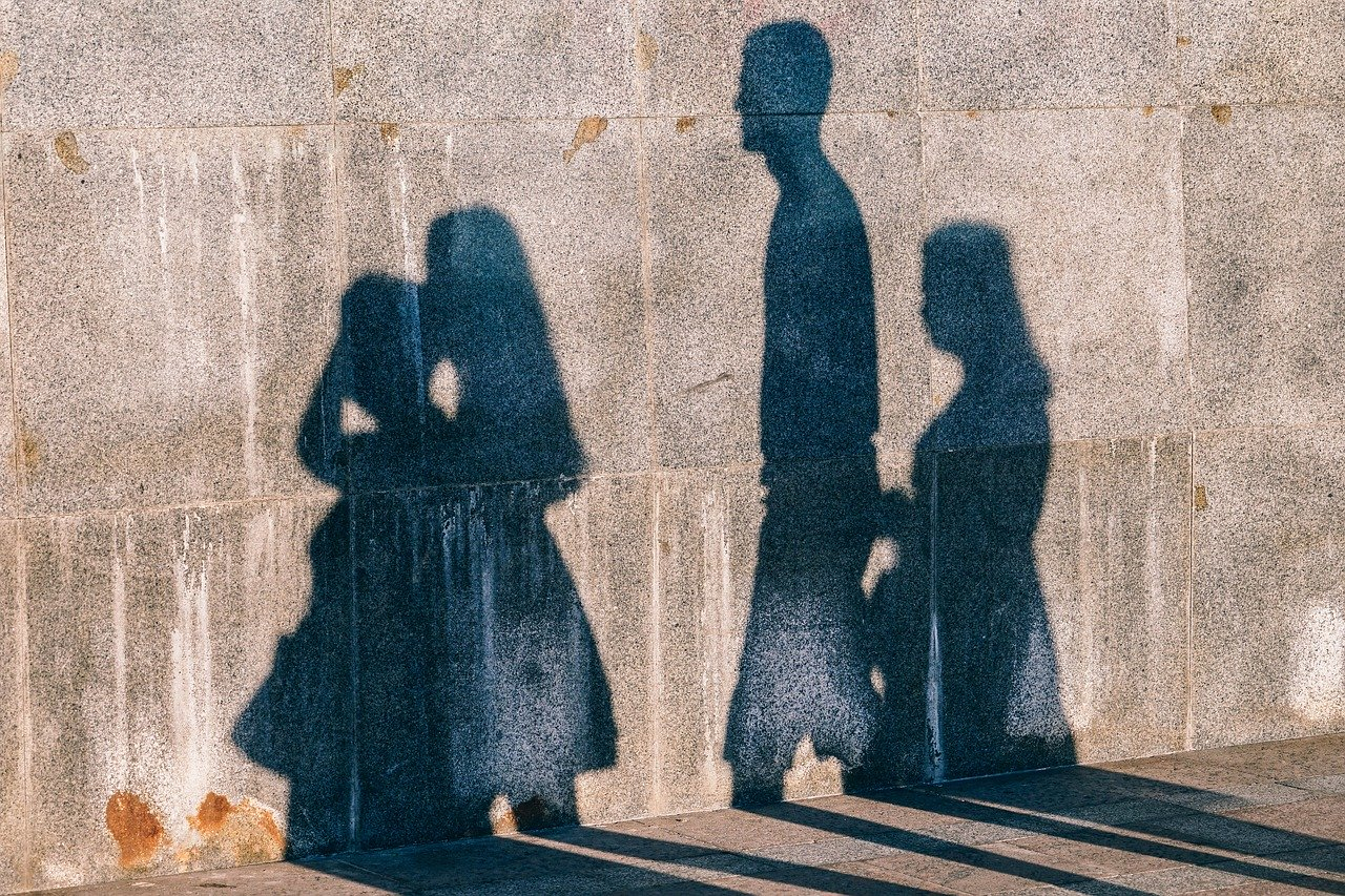 This is an image of people's silhouette against a wall on a street.