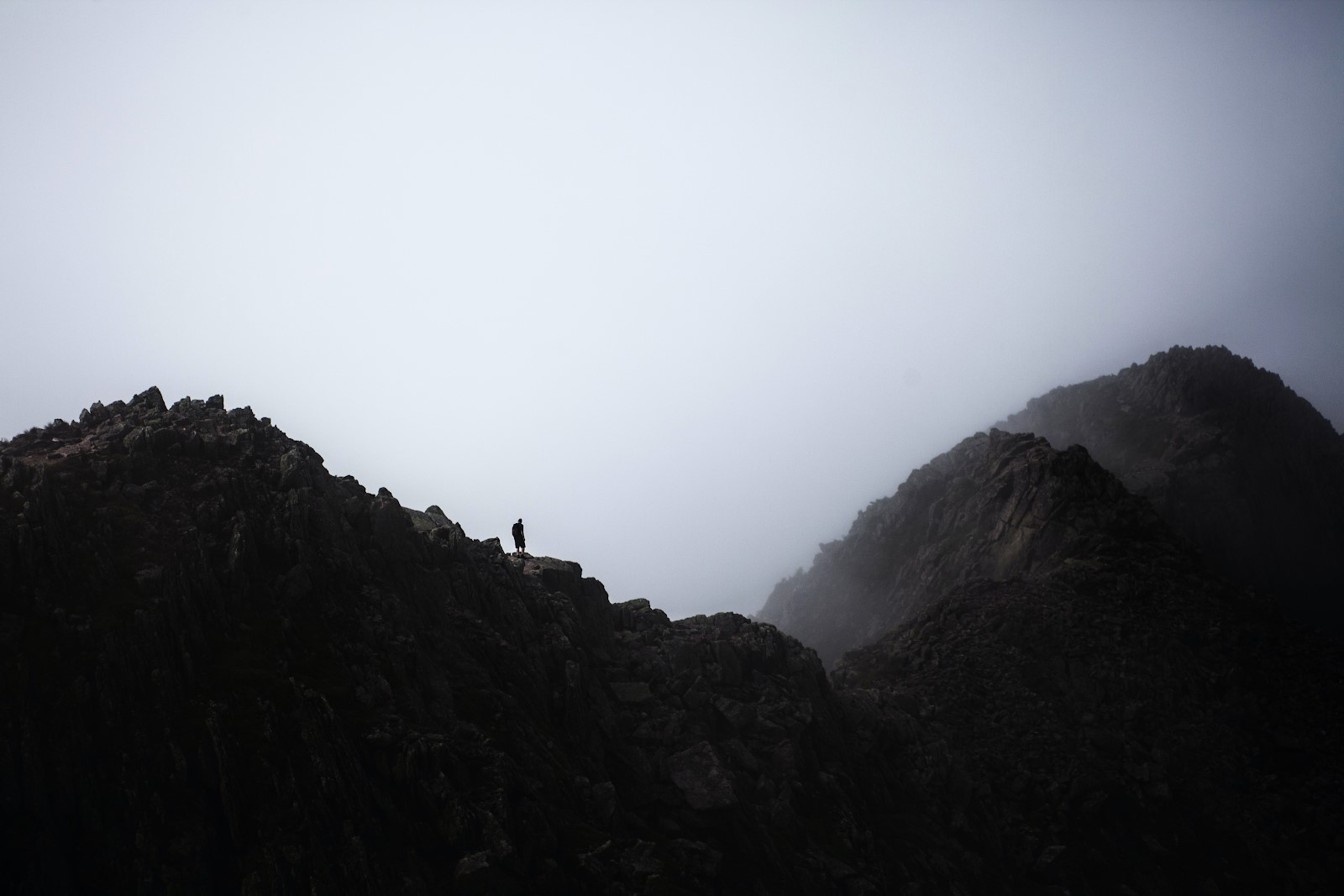 Image of Mount Katahdin in Maine with a lone figure on it silhouetted against a cloudy, misty sky.