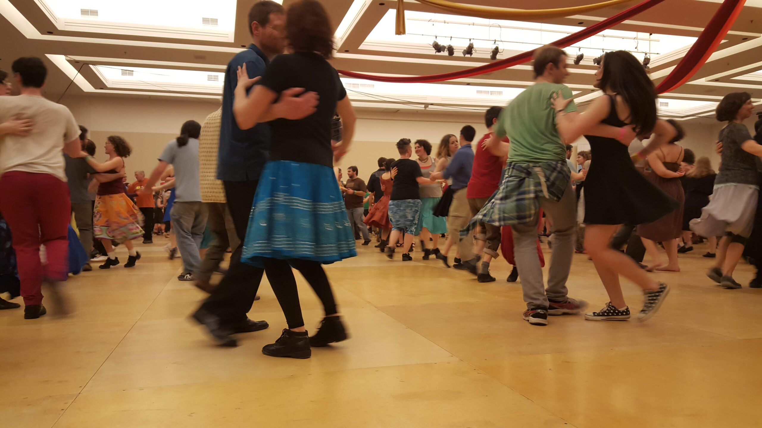 Image of lines of people contra dancing in a large room with wooden floors.