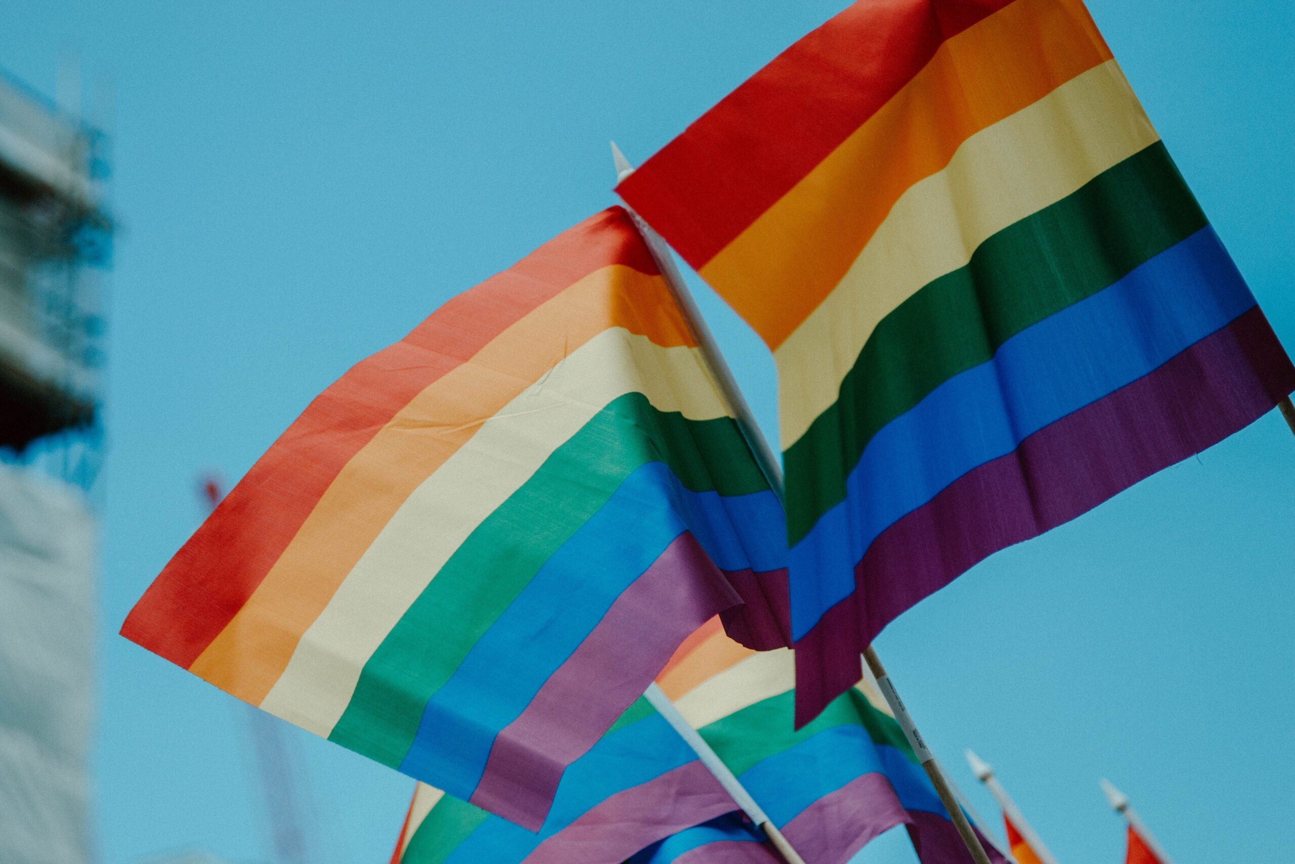 Photo of lgbt rainbow flags against a blue sky