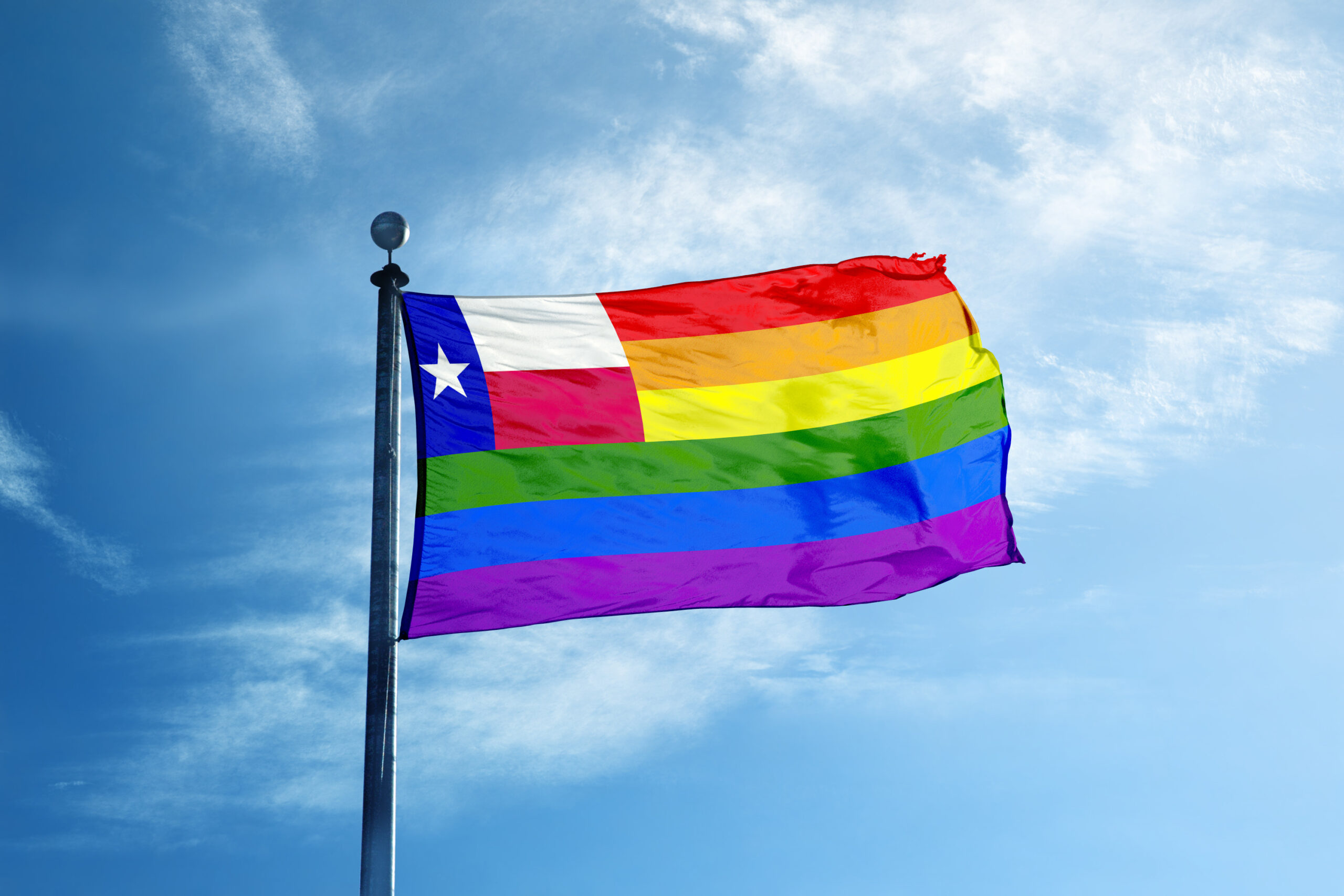 A Texas Pride flag and a clear blue sky.