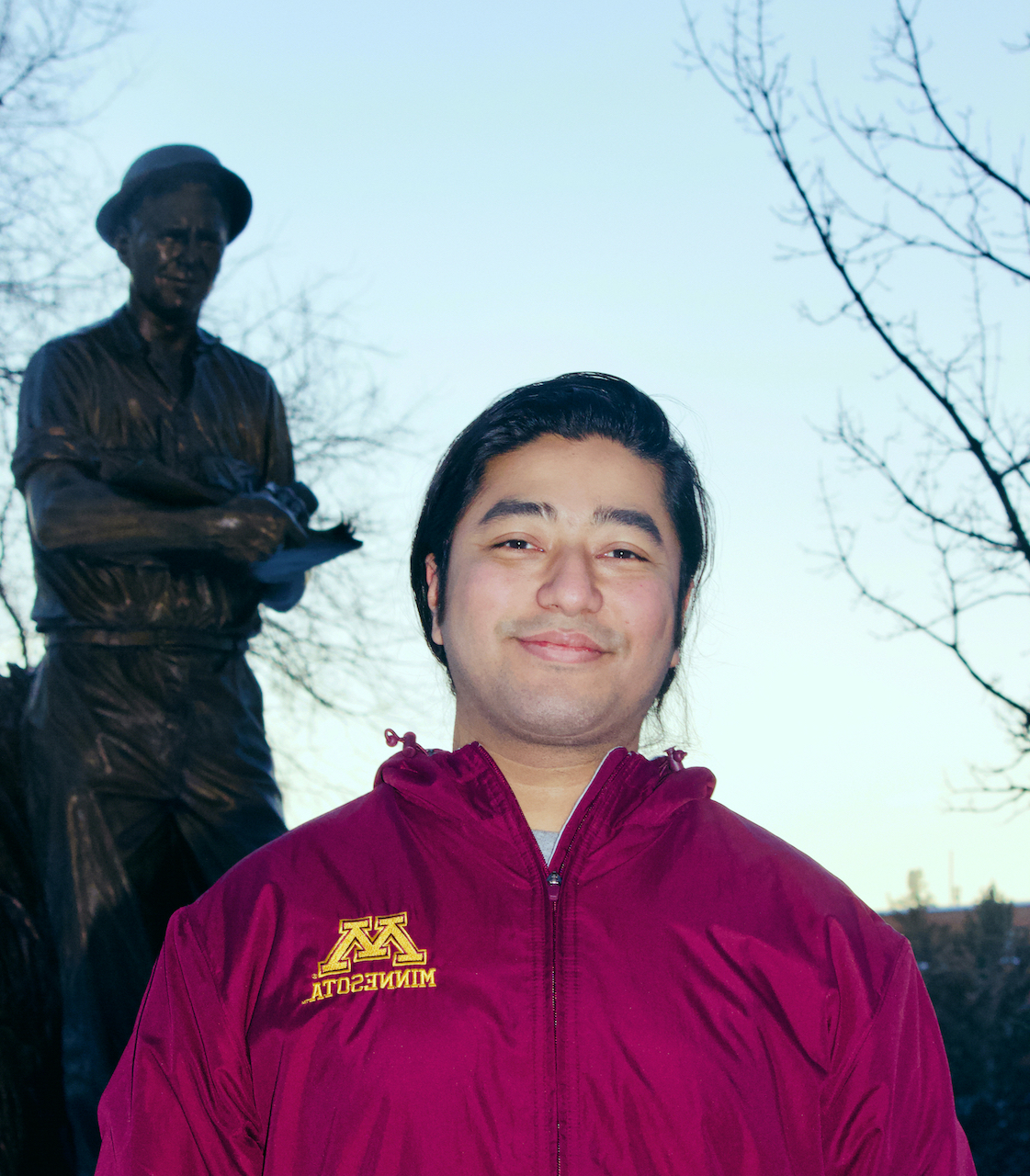 Zenith Tandukar standing in front of a statue on University of Minnesota campus