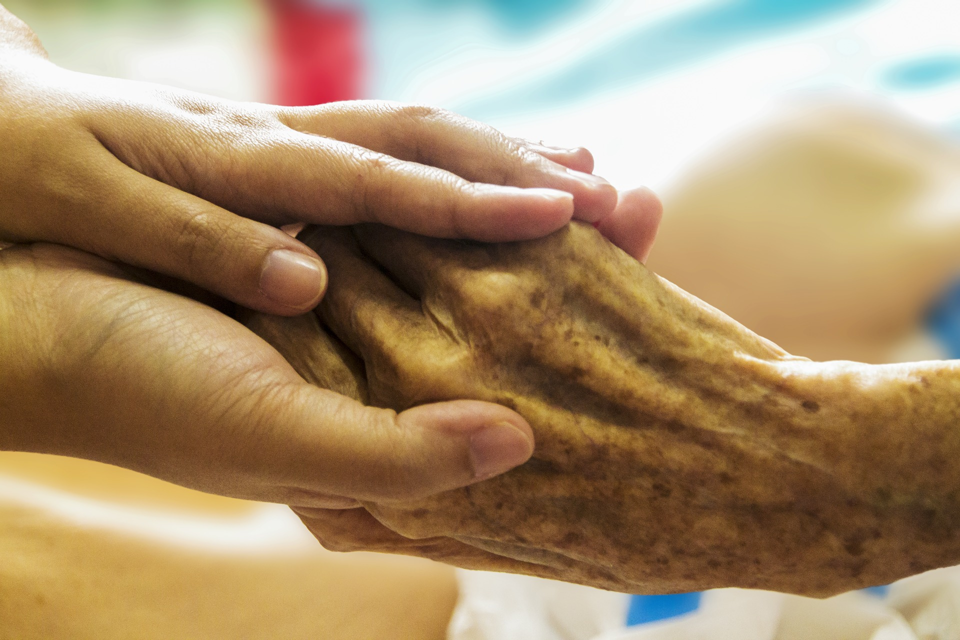 Two smaller hands grasp an older person's hand against the blurred background of a hospital room.