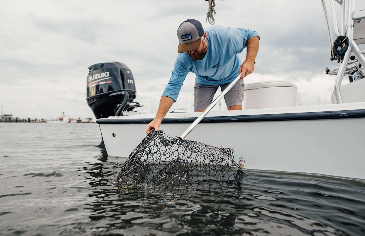 Neill Holland holds a crab trap dipped in water and stands on a white boat