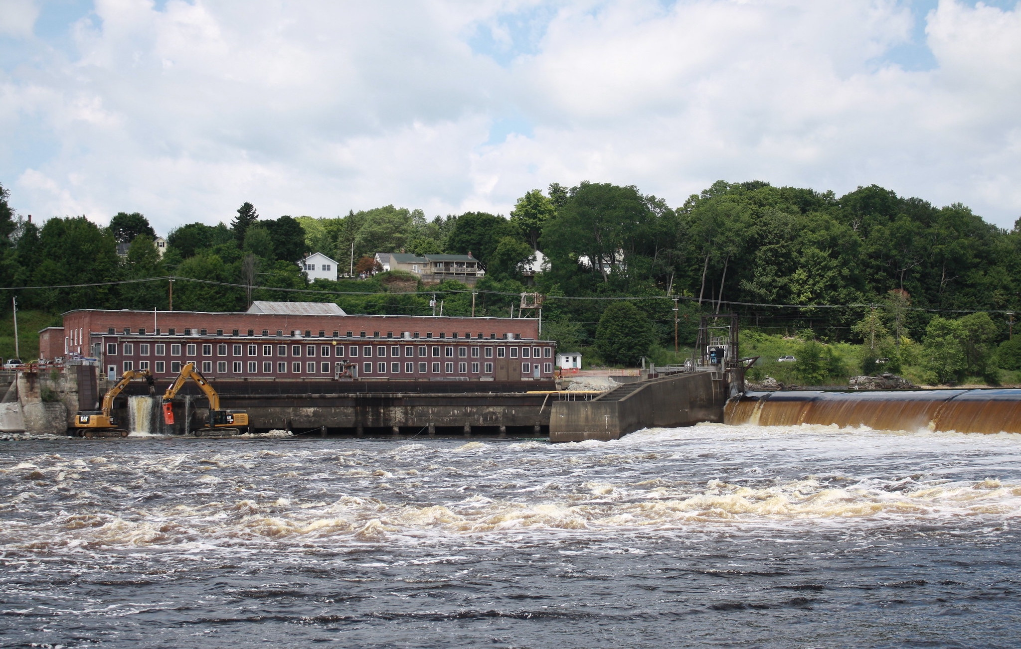 A large brick building sits on top of a big dam, with the river in the foreground. Excavators are demolishing a corner of the dam.